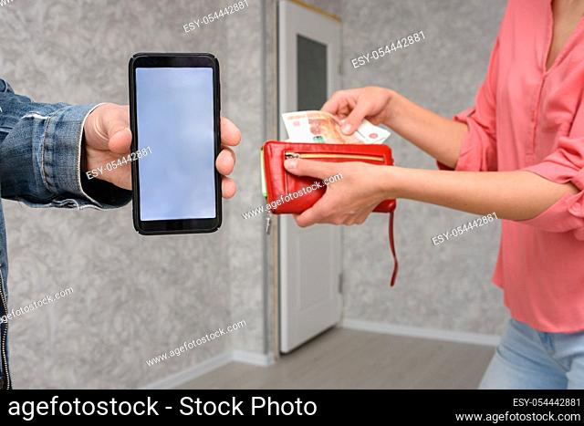 A man shows a mobile phone screen close-up, a girl takes out cash from a purse for paying for a room repair service