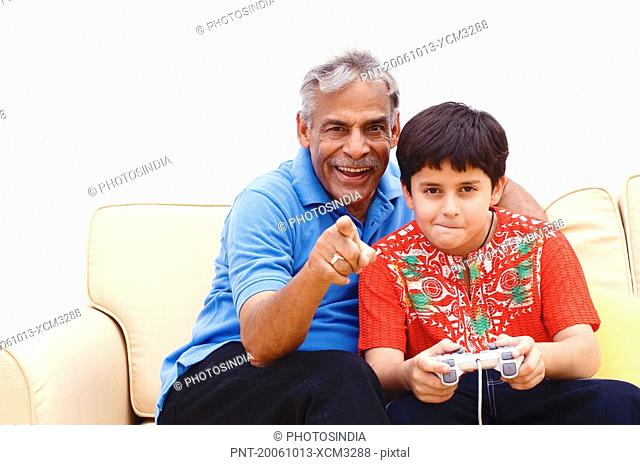 Boy and his grandfather sitting on a couch and playing a video game