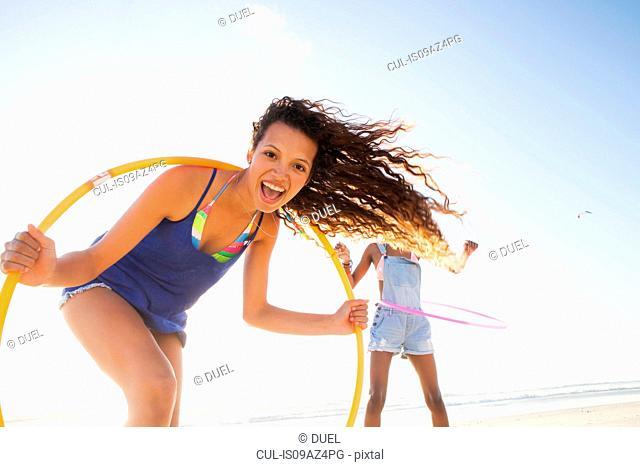 Woman holding hula hoop looking at camera smiling