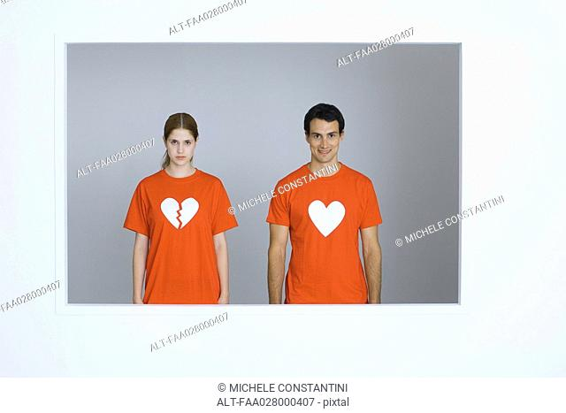Young couple wearing tee-shirts with heart symbols, woman's heart broken