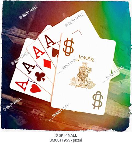 Four aces from a deck or playing cards with a jokey laying on top of them