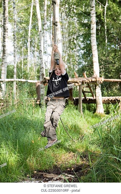 Boy swinging on a rope