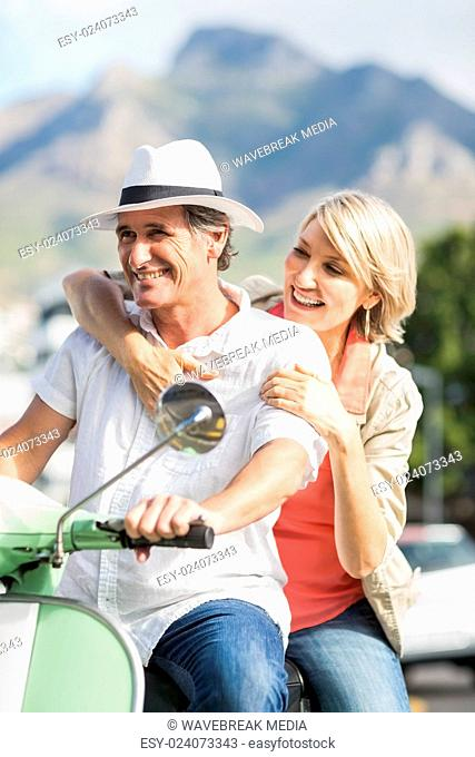 Couple riding motor scooter