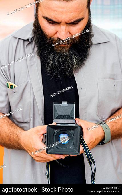 Bearded man taking photo with camera