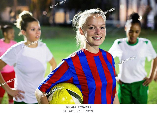 Portrait smiling, confident young female soccer player with ball on field at night