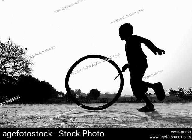 "Bangladesh â. "" January 24, 2020: A restless boy is playing on the village road with old discarded tires at Savar, Dhaka, Bangladesh"