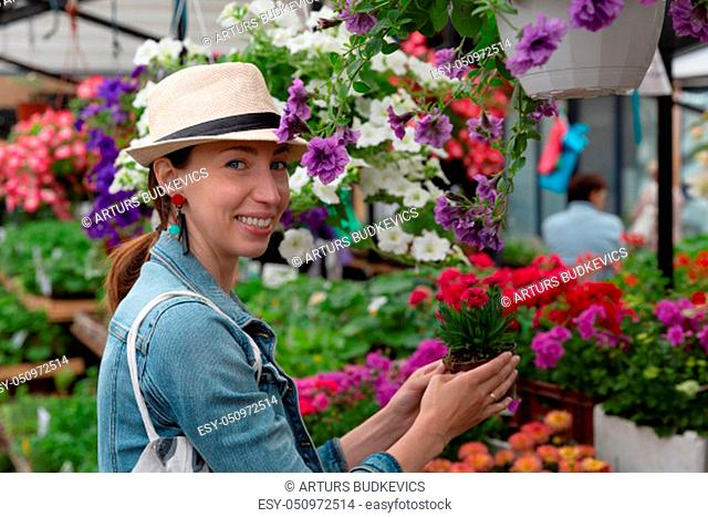 Young woman shopping in an outdoors fresh urban flowers market, buying and picking from a large variety of colorful floral bouquets during a sunny day in the...