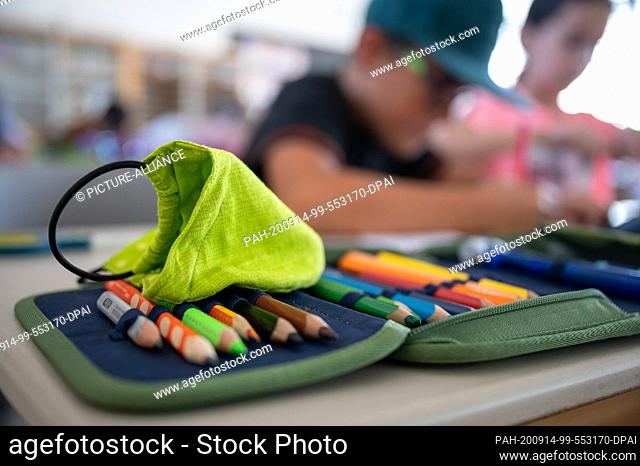 14 September 2020, Baden-Wuerttemberg, Hemmingen: A mouth and nose protector lies on a pencil case on the first day of the new school year in a primary school