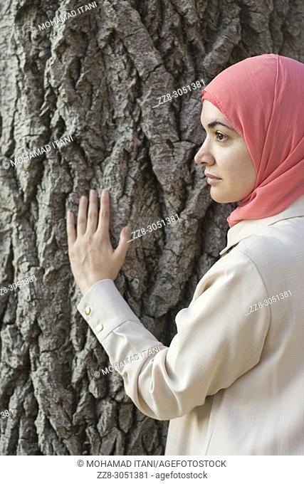Muslim woman wearing hijab hand touching tree trunk