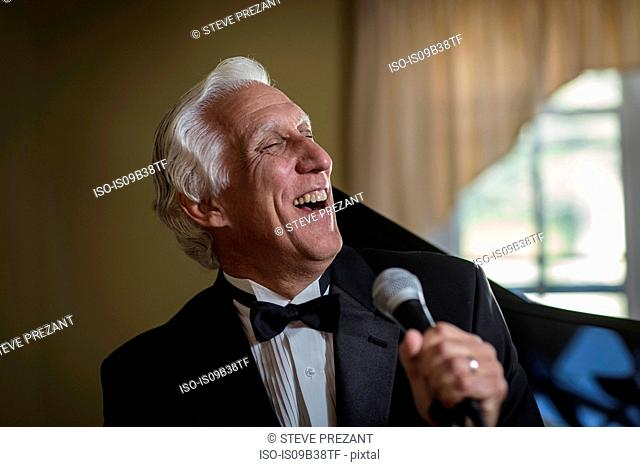 Senior man in bow tie singing into microphone