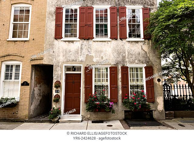 Flowers blooming in window boxes with traditional shutters along Queen Street in historic Charleston, SC