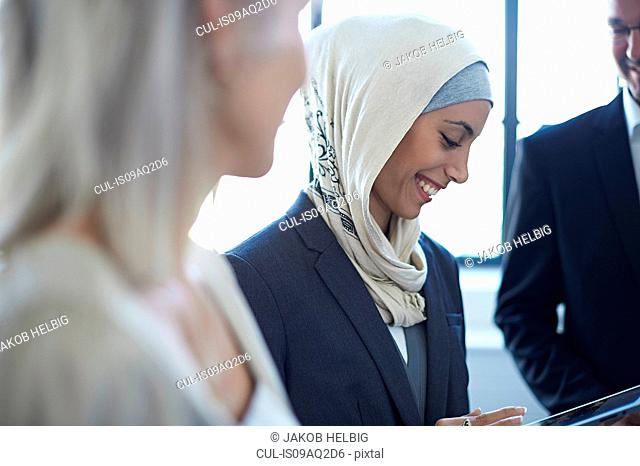 Over shoulder view of businesswomen and man chatting in office
