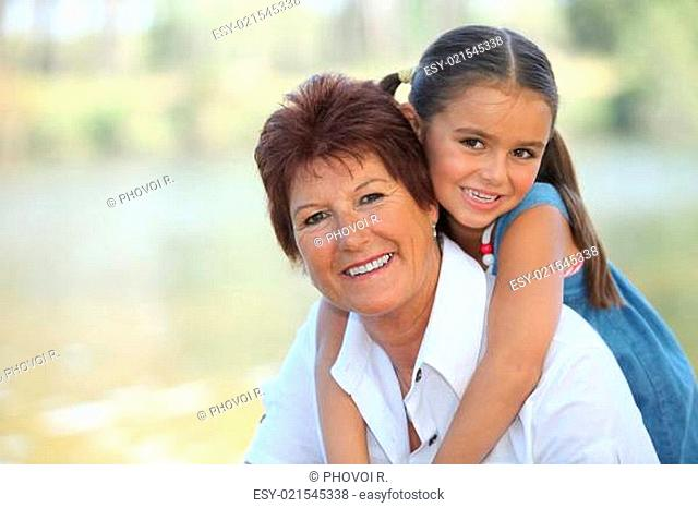 Young girl riding piggy-back on her grandmother&#039 s back