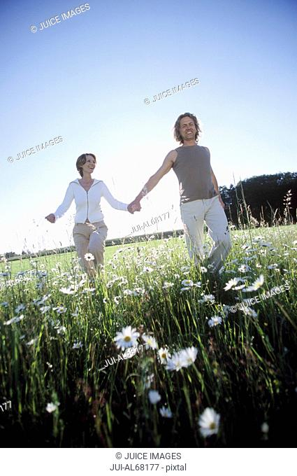 Couple holding hands and running through a field