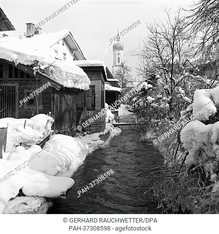 View of a stream next to snow-covered houses and the church tower in snowy Garmisch-Partenkirchen (undated archive picture from January 1963)