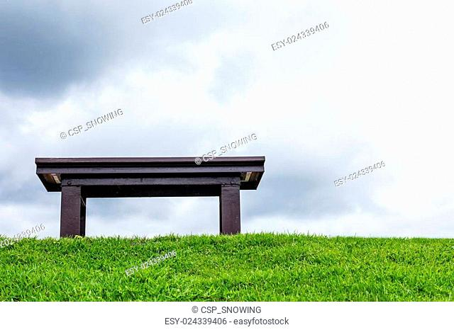 chair on a meadow with green grass and blue sky