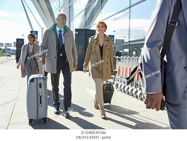 Business people walking pulling suitcases outside airport