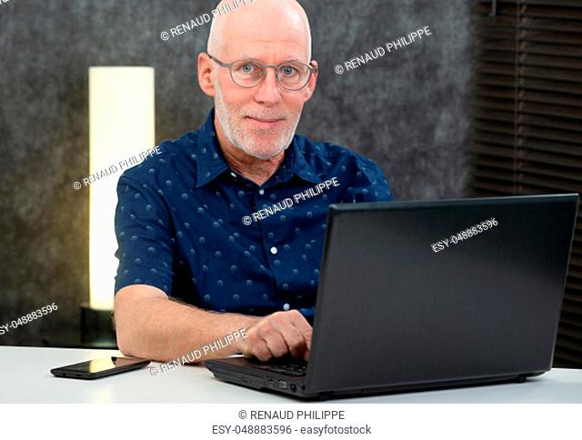 senior man with a beard and blue shirt in the office using laptop