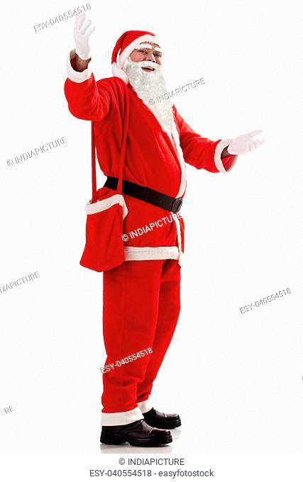 Full length of Santa Claus greeting u over white background