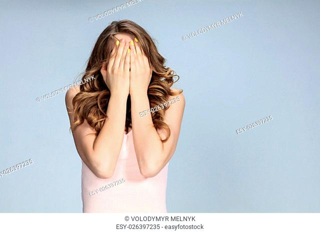 Portrait of young woman with shocked facial expression. girl covering face with hands