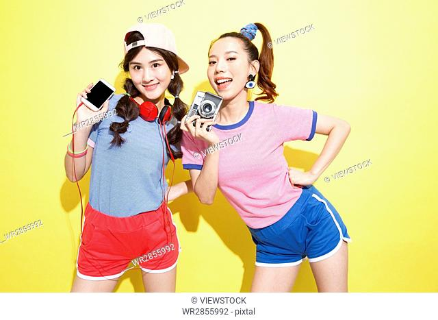Happy fashion sisters take the camera to take pictures