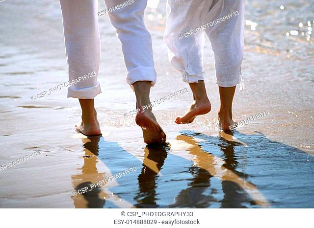 Couple walking barefoot by the sea