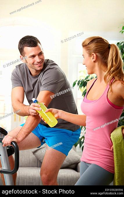 Man training on exercise bike at home, listening music