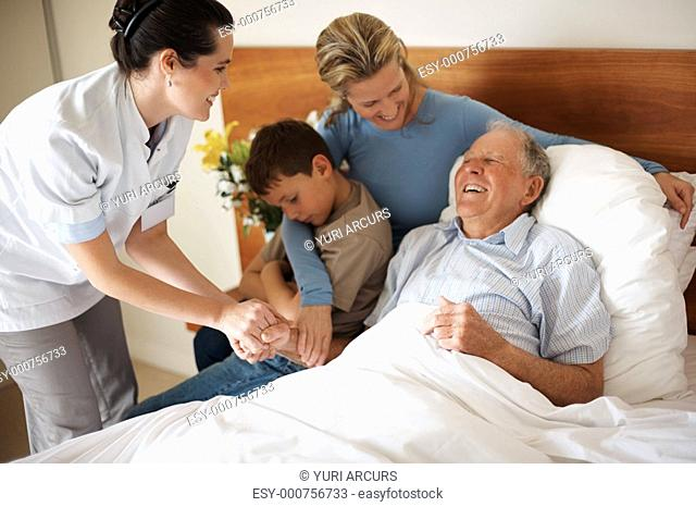 Recovered old man visited by family and doctor at the hospital