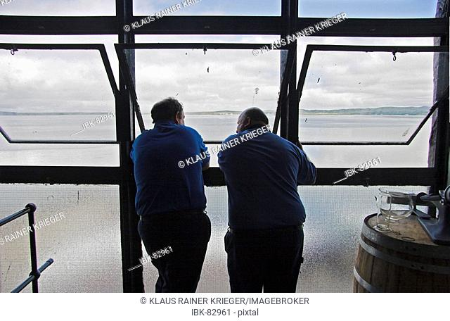 Whisky needs time.. Two workers of the Bowmore distillery looking out of the window to the ocean. Isle of Islay, Scotland