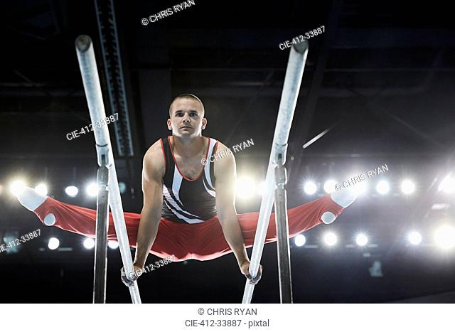 Male gymnast performing splits on parallel bars