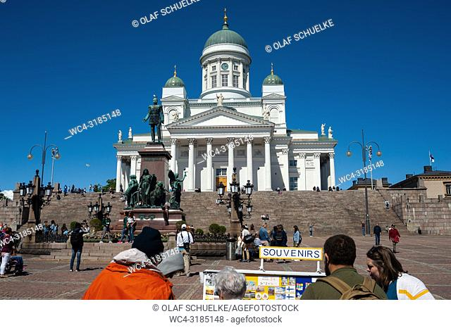 Helsinki, Finland, Europe - Toursits stand at a souvenir stall on Senate Square with the Helsinki Cathedral in the backdrop