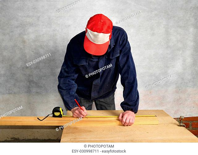 The worker measures the distance and puts a mark