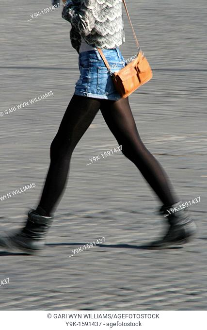 Young woman walking with bag in street in town