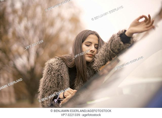sensitive woman with closed eyes relaxing on front window of car at street in city, autumn season, Munich, Germany