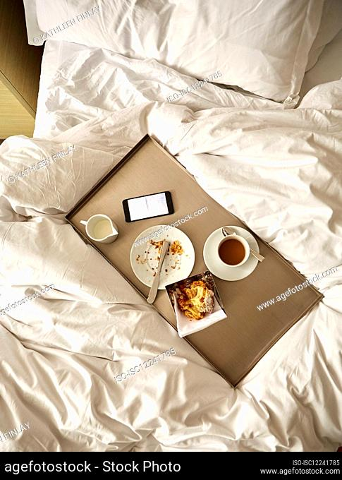 Breakfast tray with cup of coffee, smartphone, pastry and milk pot on unmade bed