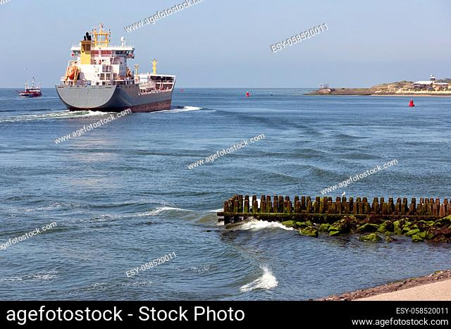 Dutch waterside of Vlissingen with a cargo ship sailing close to the coast