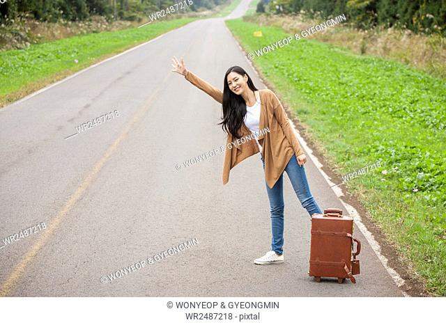 Young smiling female hitchhiker standing raising her hand on roadside with her carrier