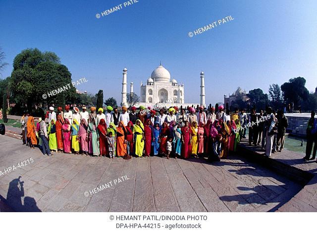 tourists standing in front of Taj mahal Seventh Wonder of The World ; Agra ; Uttar Pradesh ; India