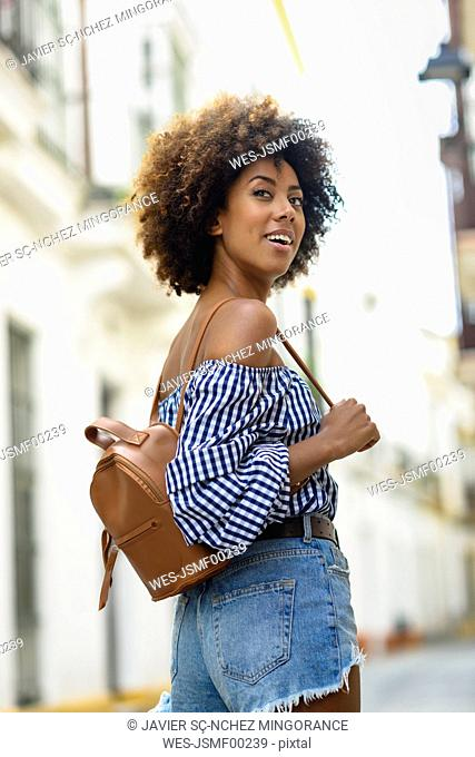 Portrait of fashionable young woman with small leather backpack