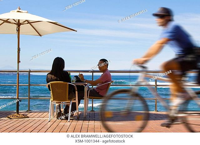 A couple sit at a beachfront table on Las Canteras Beachfront as a policeman cycles past