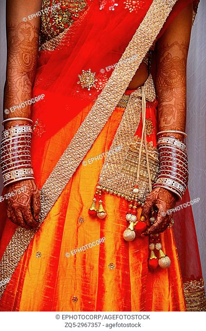 Close-up of a bride wearing beautiful silk Orange coloured Ghagra-Choli with Silver border. Pune, Maharashtra, India
