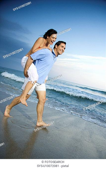 Caucasian mid-adult male carrying female piggyback style on beach
