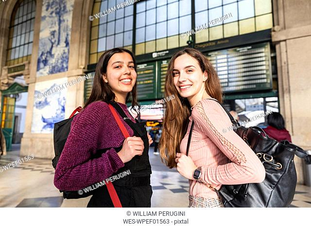 Portrait of two smiling young women with backpacks standing in front of station building, Porto, Portugal