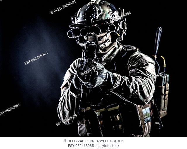 Soldier of special forces in camo combat uniform, load carrier, helmet, equipped night sight goggles, tactical radio headset