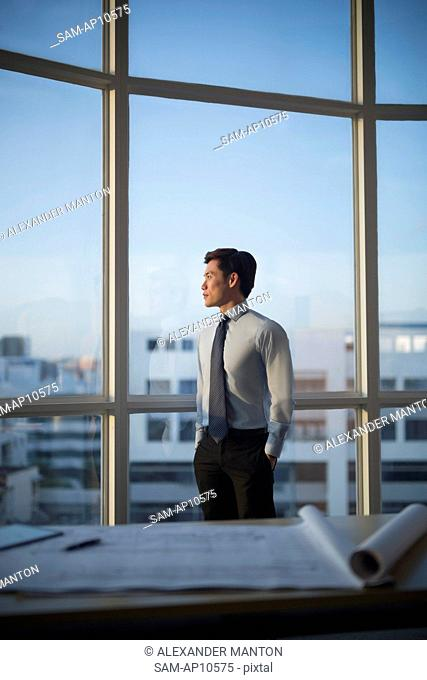 Singapore, Architect standing at window in office