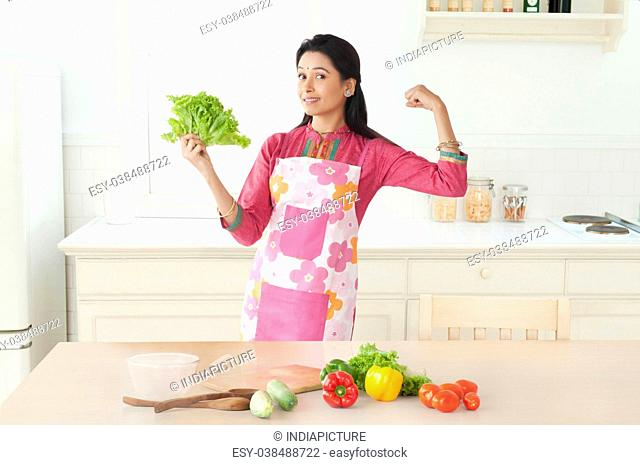 Woman holding lettuce in kitchen