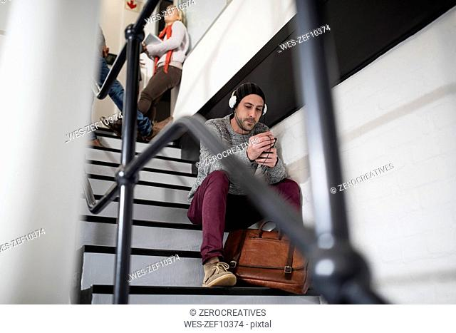 Young man with beanie and headphones sitting on stairs
