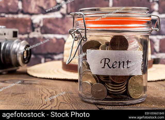 Coins in jar on wood table and brick background