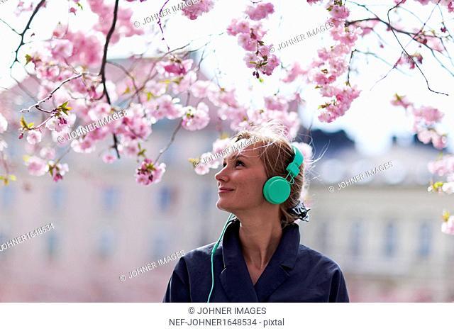Woman listening music near cherry blossom tree