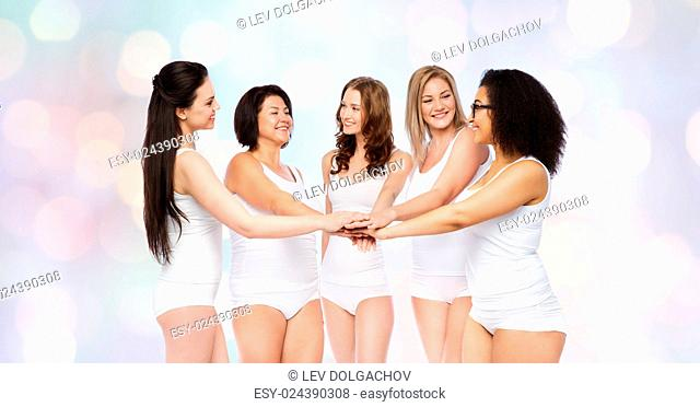 gesture, friendship, beauty, body positive and people concept - group of happy different women in white underwear holding hands together on top over holidays...